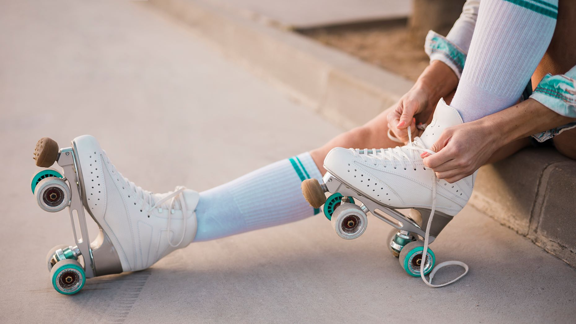 Person lacing up roller skates