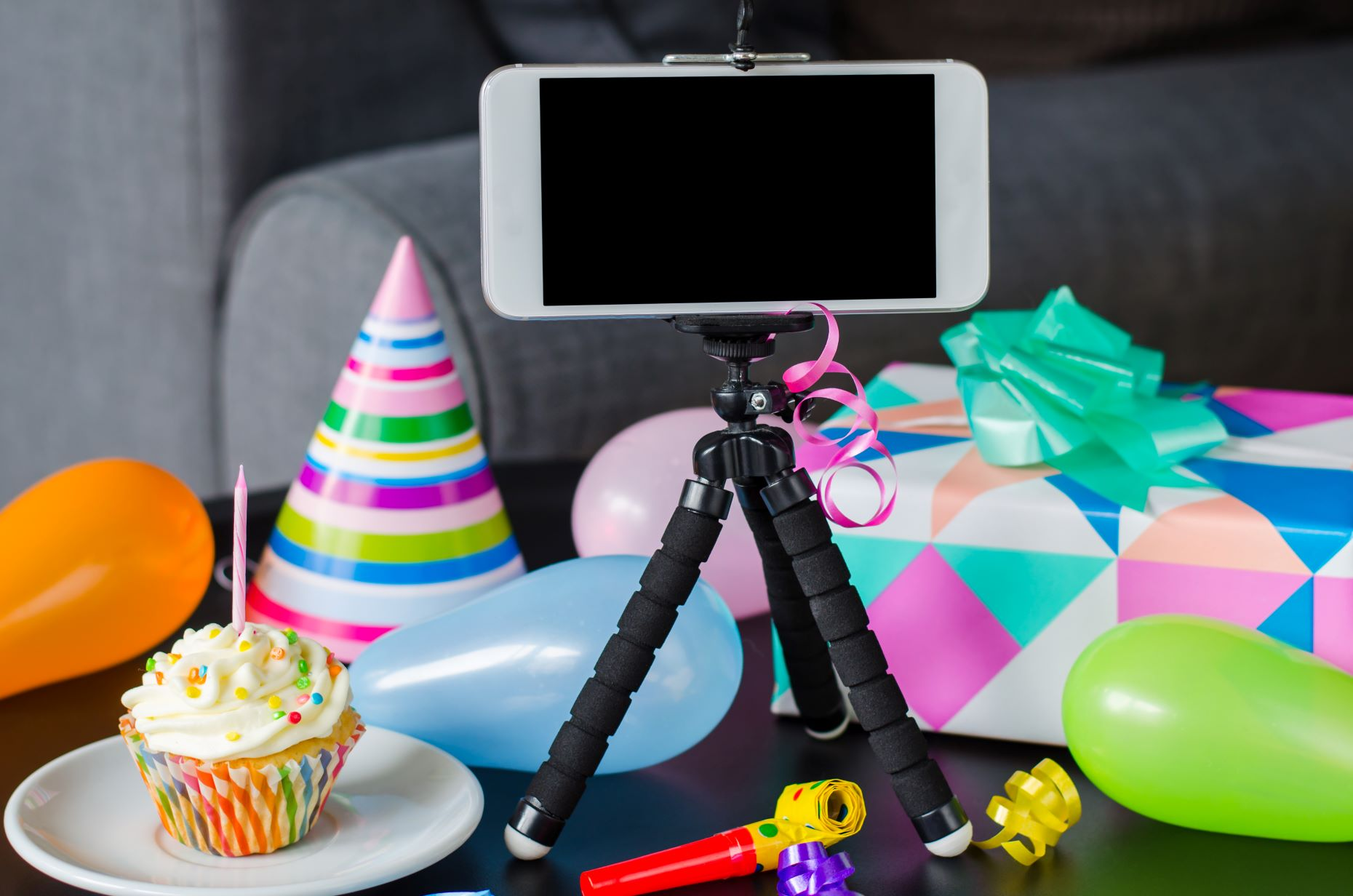 Birthday party decor around an iPhone on a mini tripod