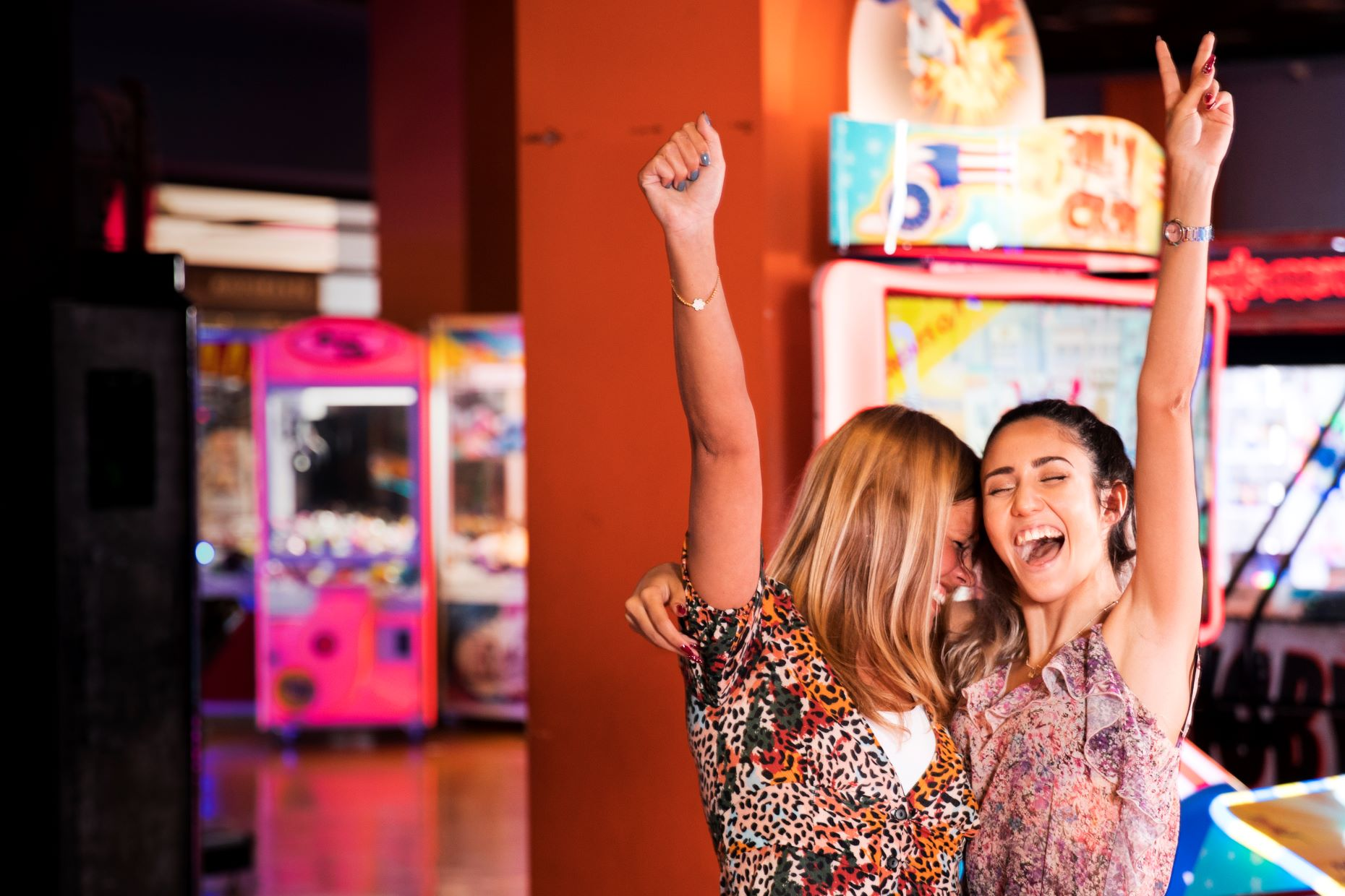 Two women at a family fun center having fun and raising hands in celebration