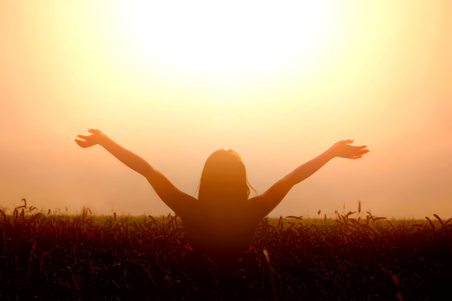 Female in a field lifting her hand up to the sky toward sun